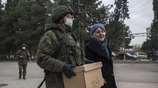 Военнослужащий российского центра по примирению враждующих сторон раздает гуманитарную помощь жителям города Мартакерт в Нагорном Карабахе