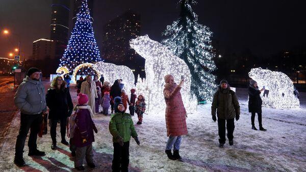 Прохожие у новогодней инсталляции в парке