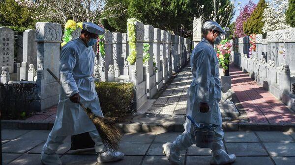 Рабочие моют надгробные камни на кладбище в Китае