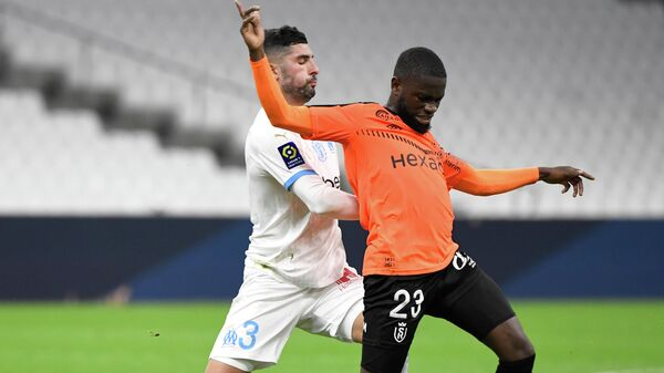 Marseille's Spanish defender Alvaro Gonzalez (L) fights for the ball with Reims' Bissau-Guinean midfielder Moreto Cassama during the French L1 football match between Olympique de Marseille (OM) and Reims at the Velodrome Stadium in Marseille, southeastern France, on December 19, 2020. (Photo by NICOLAS TUCAT / AFP)