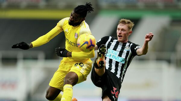 Fulham's Cameroonian midfielder Andre-Frank Zambo Anguissa (L) and Newcastle United's English midfielder Sean Longstaff compete during the English Premier League football match between Newcastle United and Fulham at St James' Park in Newcastle-upon-Tyne, north east England on December 19, 2020. (Photo by Owen Humphreys / POOL / AFP) / RESTRICTED TO EDITORIAL USE. No use with unauthorized audio, video, data, fixture lists, club/league logos or 'live' services. Online in-match use limited to 120 images. An additional 40 images may be used in extra time. No video emulation. Social media in-match use limited to 120 images. An additional 40 images may be used in extra time. No use in betting publications, games or single club/league/player publications. /