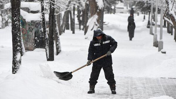 Дворник убирает снег в сквере