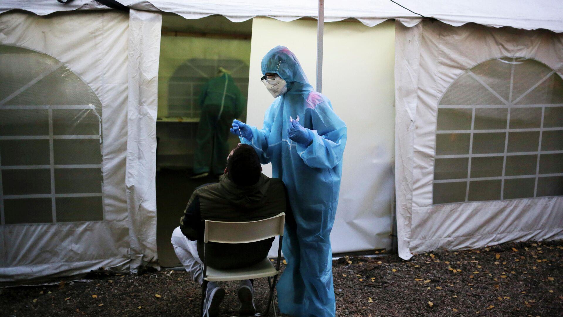 Медик в защитном костюму берет мазок у пациента во время тестирования на SARS CoV-2 в Берлине - РИА Новости, 1920, 23.12.2020
