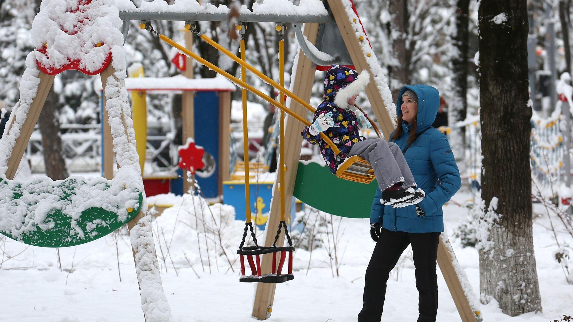 Женщина с ребенком на детской площадке Фестивального сквера в Краснодаре после снегопада - РИА Новости, 1920, 23.12.2020