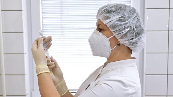 Медицинский работник набирает в шприц препарат Гам-Ковид-Вак во время вакцинации от короновируса