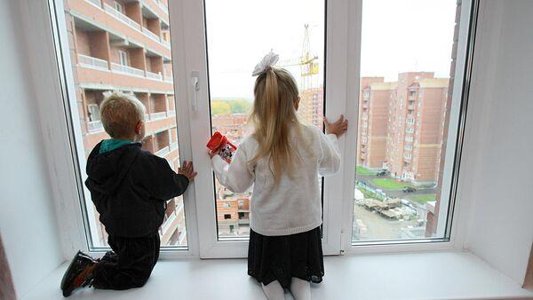 Дети смотрят в окно из новой квартиры