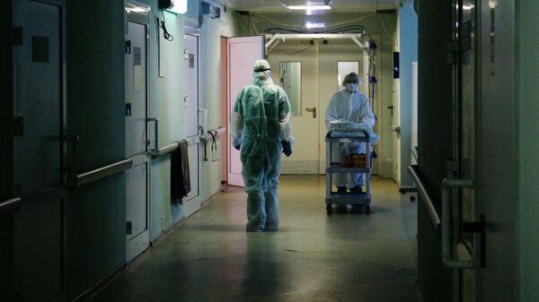 Медики в защитном противоэпидемическом костюме в коридоре Новосибирской областной клинической больницы