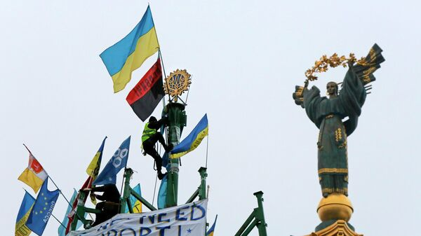 Активист проевропейского союза укрепляет украинский герб и флаг на металлической основе разрушенной елки во время митинга на площади Независимости в Киеве