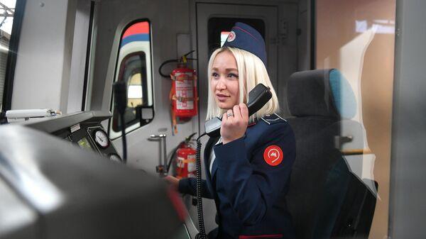 Машинистка в головном вагоне поезда на одной из станций московского метрополитена