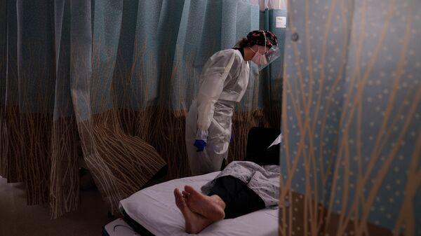 Медсестра разговаривает с пациентом, у которого проявляются симптомы коронавируса, в отделении неотложной помощи Медицинского центра в Лос-Анджелесе