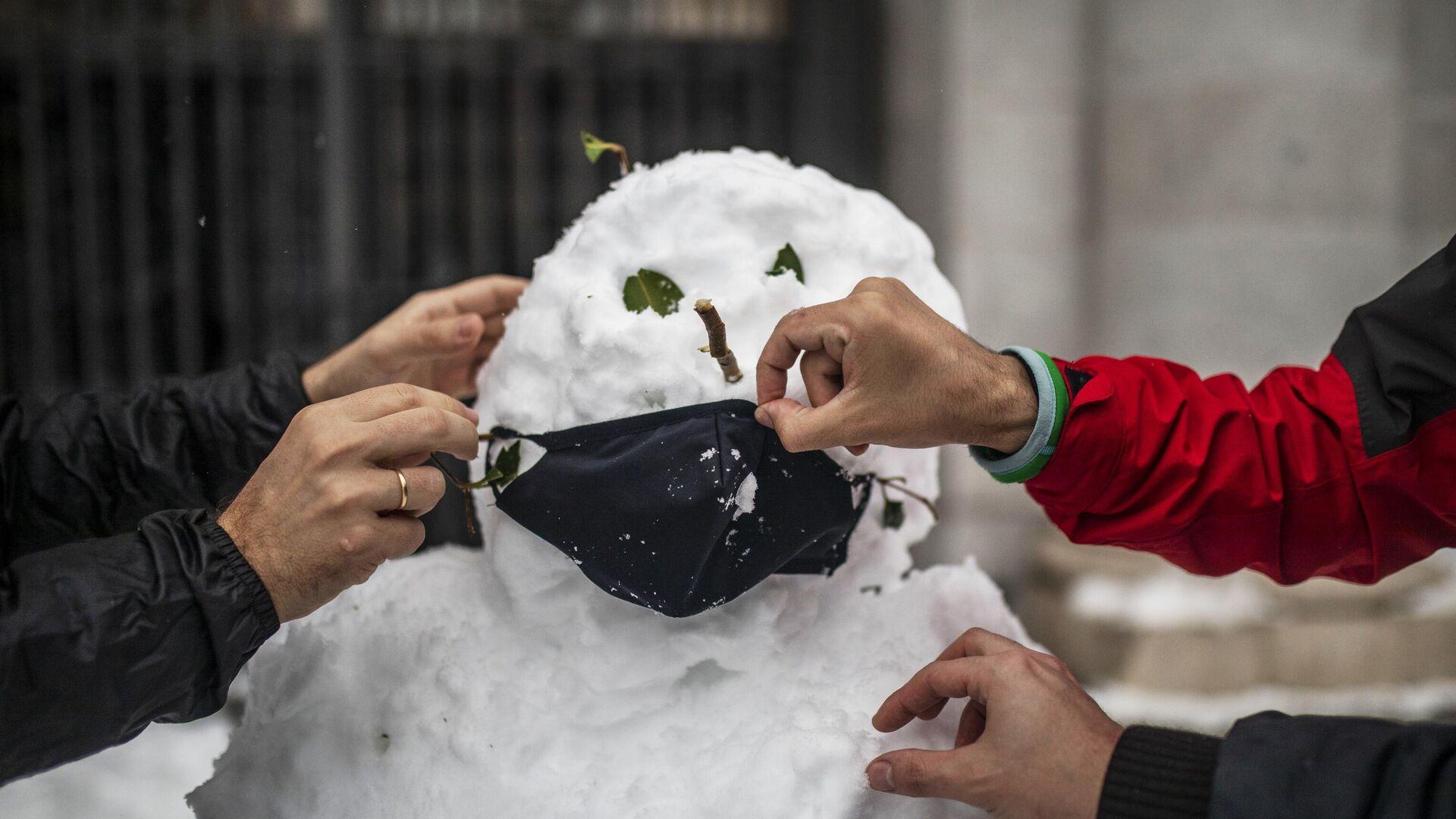 Люди надевают маску на слепленного снеговика на одной из улиц в Мадриде - РИА Новости, 1920, 02.02.2021