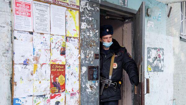 Сотрудник полиции в подъезде жилого дома на улице Рассветной в Екатеринбурге, где произошел пожар