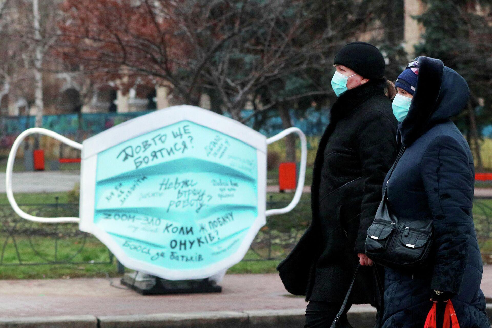Женщины проходят мимо инсталляции в виде защитной маски на улице в Киеве - РИА Новости, 1920, 16.01.2021