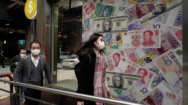 Люди на фоне обменного пункта в одном из районов Гонконга в Китае