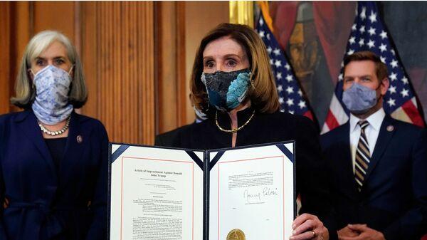 Спикер Палаты представителей конгресса США Нэнси Пелоси демонстрирует подписанный документ об импичменте президенту Дональду Трампу