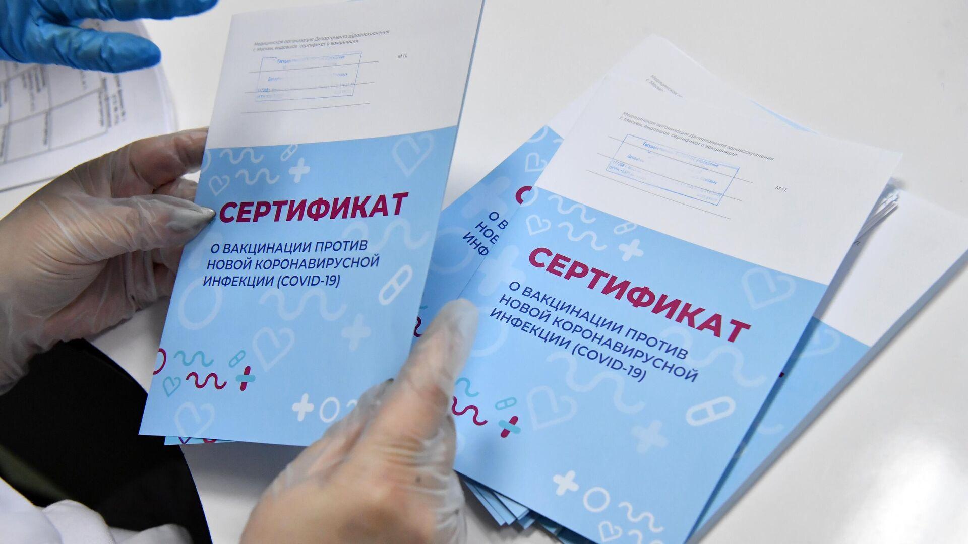 Медработник с сертификатами о вакцинации от новой коронавирусной инфекции COVID-19, которые выдаются пациентам после вакцинации вакциной Спутник V - РИА Новости, 1920, 04.03.2021