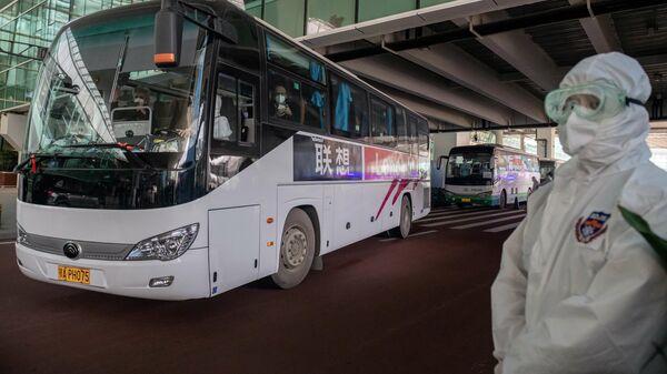 Группа экспертов ВОЗ садятся в автобус перед отъездом из международного аэропорта Ухань