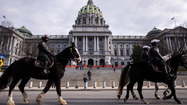 Конная полиция дежурит неподалеку от здания Капитолия штата Пенсильвания в Гаррисберге