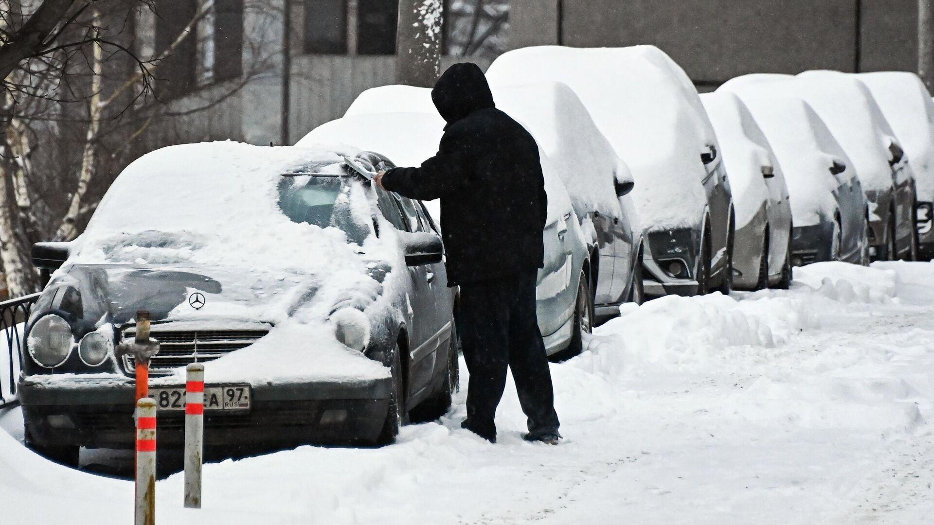 Мужчина очищает автомобиль от снега в Москве - РИА Новости, 1920, 18.01.2021