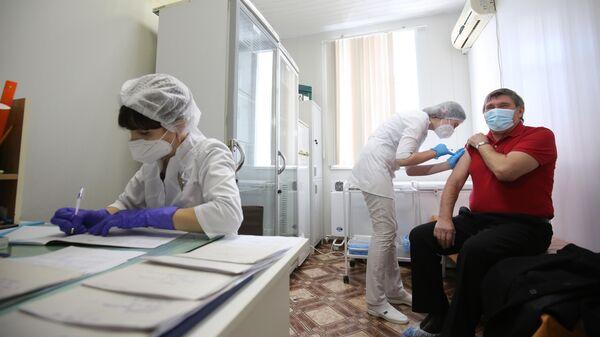 Медсестра делает прививку пациенту от коронавируса вакциной Спутник-V (Гам-КОВИД-Вак) в районной больнице Волгограда
