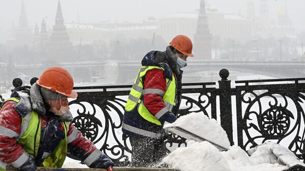 Рабочие расчищают от снега и наледи Патриарший мост в Москве