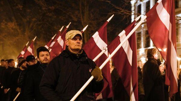 Участники факельного шествия в честь Дня независимости Латвии в Риге