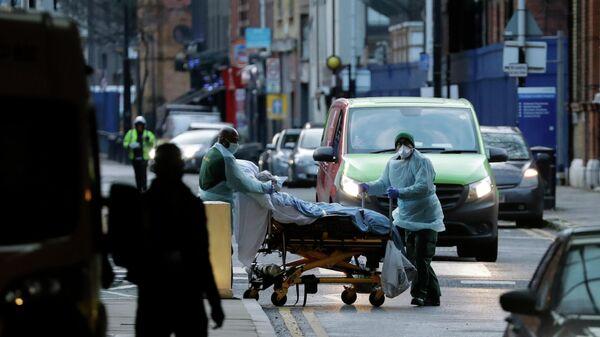 Медицинские работники транспортируют пациента на улице Лондона, Великобритания