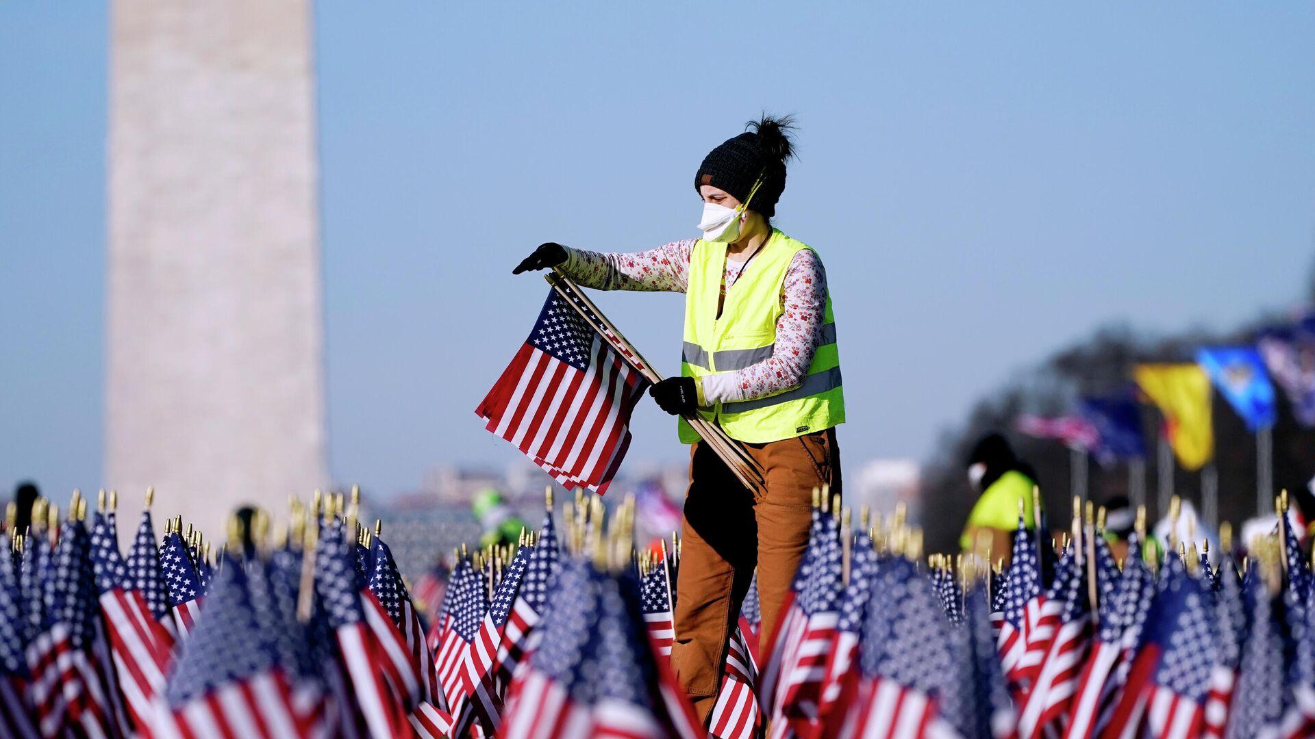 Женщина убирает флаги с Национальной аллеи после инаугурации президента США Джо Байдена в Вашингтоне - РИА Новости, 1920, 29.01.2021