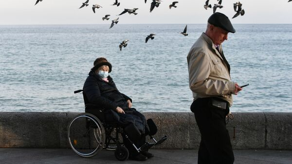 Люди гуляют по набережной Ялты