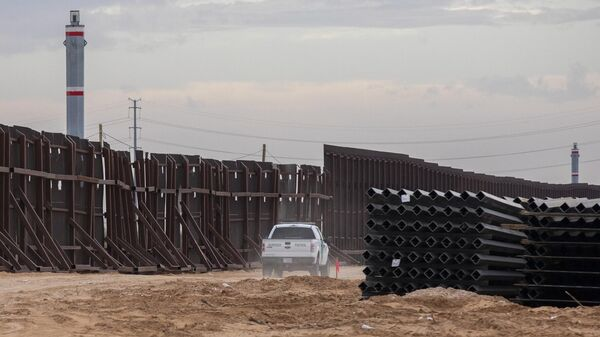 Машина пограничного патруля США едет вдоль конструкций недостроенной стены на границе между США и Мексикой