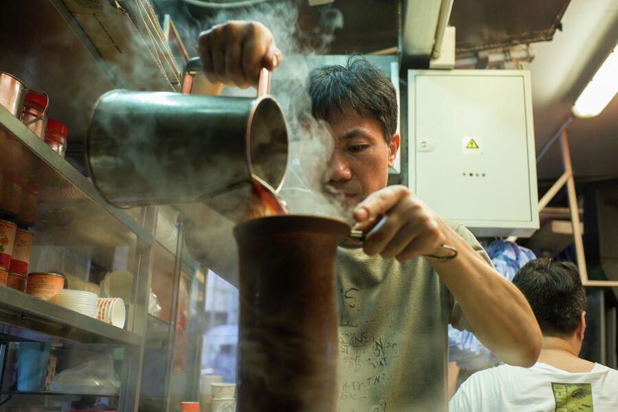 Мастер готовит чай с молоком в чайном магазине в Гонконге