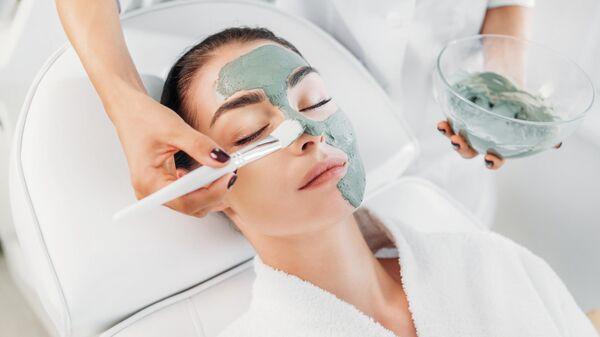 Косметолог делает маску из глины девушке в спа-салоне