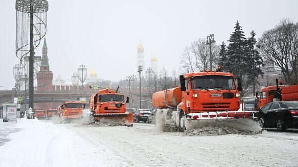 Снегоуборочные машины чистят автомобильную дорогу на Москворецкой набережной в Москве