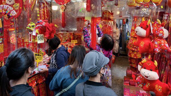 Торговля праздничными декоративными украшениями на уличном рынке во время подготовки к предстоящему Китайскому Новому году в Гонконге