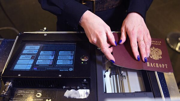 Сотрудник транспортной полиции сканирует паспорт пассажира комплексом для проверки лиц и документов
