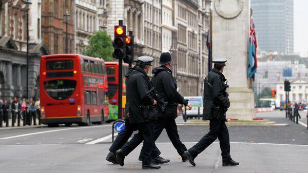 Полицейские переходят дорогу у здания Министерства иностранных дел и международного развития в Лондоне