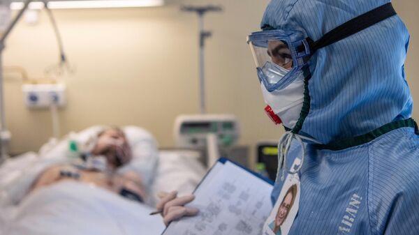 Медицинский работник и пациент c COVID-19 в отделении реанимации и интенсивной терапии в НИИ скорой помощи им. Н. В. Склифосовского в Москве