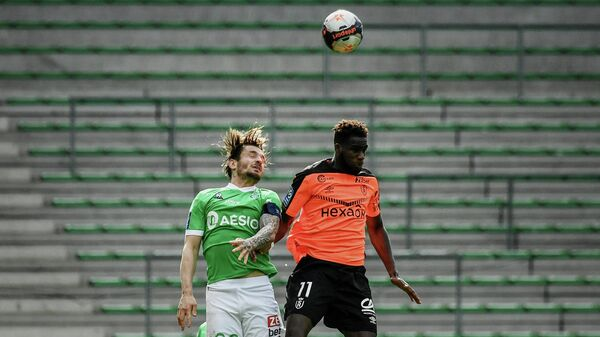 Reims' French midfielder Boulaye Dia (R) fights for the ball with Saint-Etienne's French defender Mathieu Debuchy (L) during the French L1 football match AS Saint-Etienne (ASSE) vs Stade de Reims (SR) on February 20, 2021, at the Geoffroy Guichard stadium in Saint-Etienne. (Photo by JEFF PACHOUD / AFP)