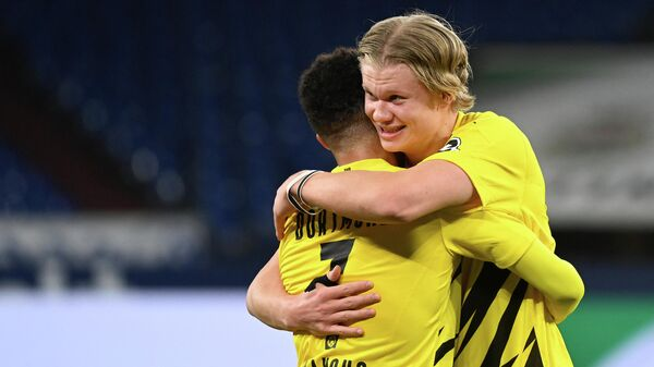 Dortmund's Norwegian forward Erling Braut Haaland (R) celebrates with Dortmund's English midfielder Jude Bellingham after the German first division Bundesliga football match FC Schalke 04 vs Borussia Dortmund in Gelsenkirchen, western Germany, on February 20, 2021. - Dortmund won the match 4-0. (Photo by Ina Fassbender / various sources / AFP) / RESTRICTIONS: DFL REGULATIONS PROHIBIT ANY USE OF PHOTOGRAPHS AS IMAGE SEQUENCES AND/OR QUASI-VIDEO