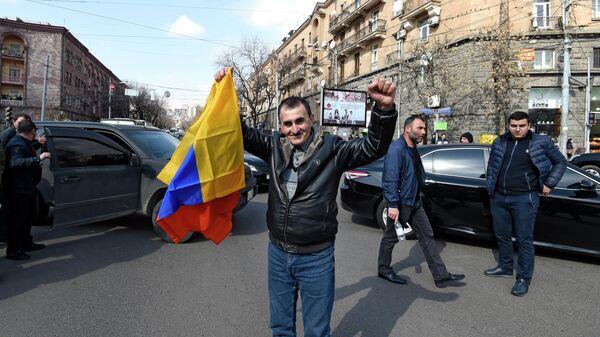 Мужчина с национальным флагом на проспекте Баграмяна в Ереване