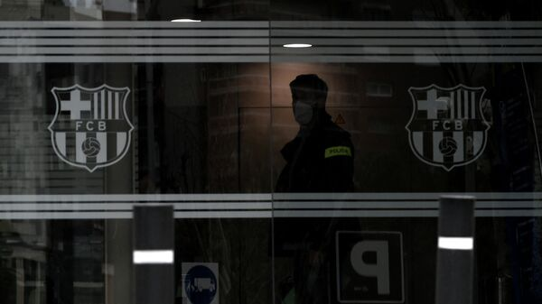 A policeman stands in the offices of the Barcelona Football Club on March 01, 2021 in Barcelona during a police operation inside the building. - Police raided the offices of FC Barcelona on March 01, 2021, carrying out several arrests just six days ahead of the club's presidential elections, a Catalan regional police spokesman told AFP. Spain's Cadena Ser radio said one of those arrested was former club president Josep Maria Bartomeu, who resigned in October, along with CEO Oscar Grau and the club's head of legal services. (Photo by LLUIS GENE / AFP)
