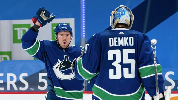 VANCOUVER, BC - MARCH 08: Jayce Hawryluk #13 of the Vancouver Canucks congratulates teammate Thatcher Demko #35 after defeating the Montreal Canadiens 2-1 in a shootout in NHL hockey action at Rogers Arena on March 8, 2021 in Vancouver, Canada.   Rich Lam/Getty Images/AFP (Photo by Rich Lam / GETTY IMAGES NORTH AMERICA / Getty Images via AFP)