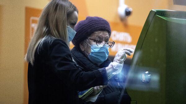 Сотрудница в отделении Сбера помогает женщине у банкомата