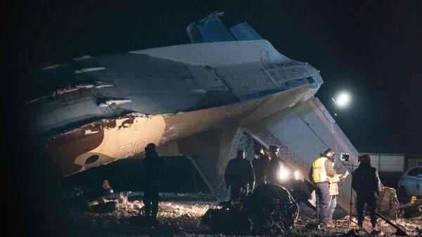 Сотрудники специальных служб на месте крушения военно-транспортного самолета Ан-26 в аэропорту Алматы