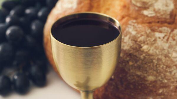 Чаша с вином на фоне хлеба и винограда