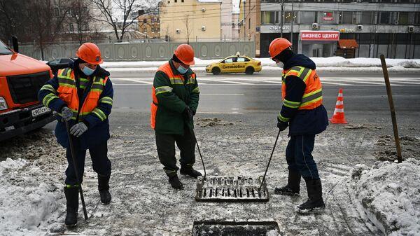 Сотрудники ГУП Мосводосток во время очистки водоприемных колодцев в Москве