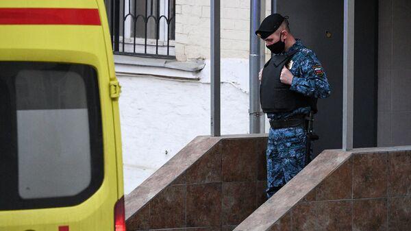 Сотрудник Федеральной службы судебных приставов (ФССП) и автомобиль скорой помощи у здания Басманного суда города Москвы