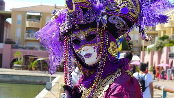Артист в карнавальной маске в Венеции