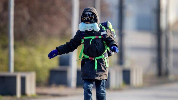 Мальчик в защитной маске идет в школу во Франкфурте, Германия