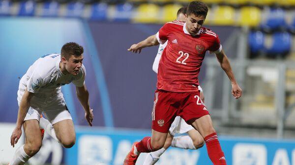 Игрок молодежной сборной Исландии Ари Лейфссон и игрок молодежной сборной России Арсен Захарян (справа) в матче 1-го тура группового этапа чемпионата Европы по футболу 2021 среди молодежных команд между сборными России и Исландии.